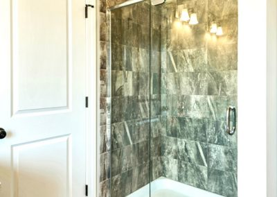 tiled shower with clear glass door