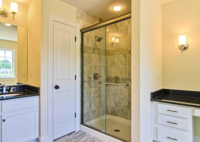 makeup counter with tiled shower and glass door