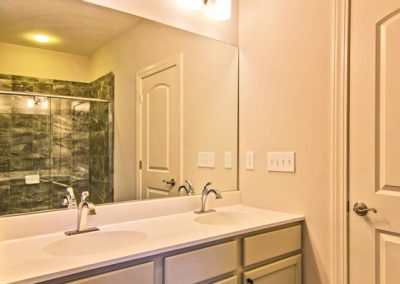 white dual vanity with shower shown in mirror