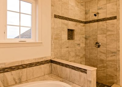 tiled oval bathtub with custom shower