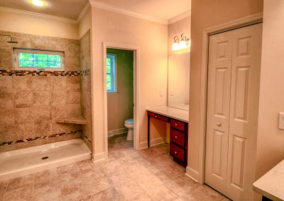 tiled shower with makeup vanity and wc