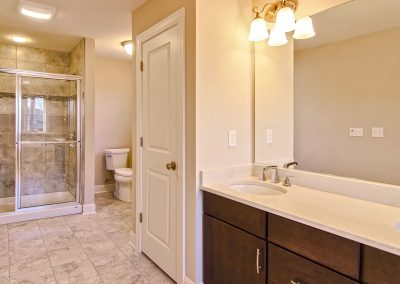 double vanity with large mirror and tiled shower with bench