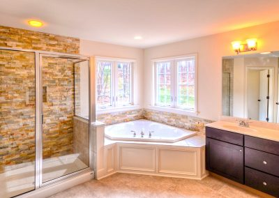shower corner tub with stone wall and double vanity