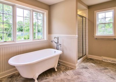 custom claw foot tub with window and subway tiled shower