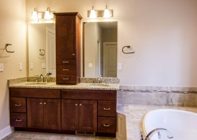 double vanity with upper cabinet and oval tub
