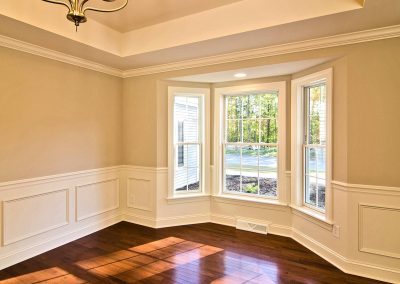 dining room with wall molding tray ceiling and bay window