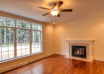 family room with hardwood fireplace and ceiling fan