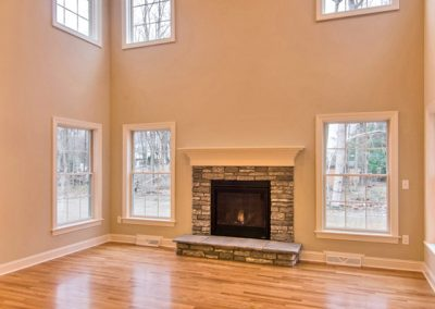 two story room with hardwood floor and raised stone hearth