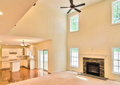 two story family room with ceiling fan and fireplace