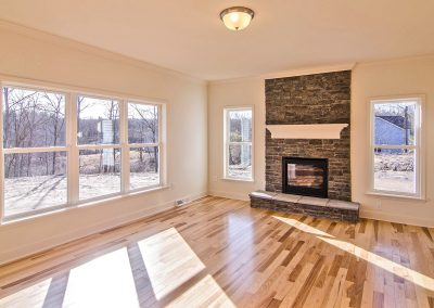 family room with stone fierplace and hardwood flooring