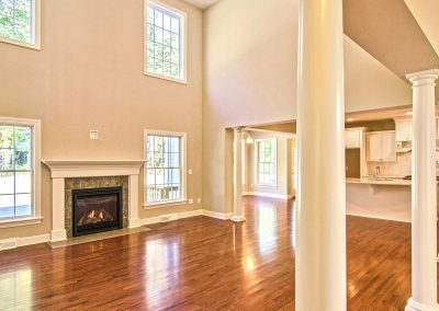 two story family room with columns and fireplace