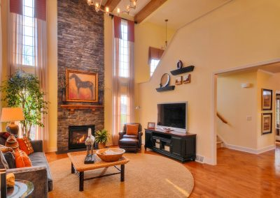 furnished two story family room with stone fireplace