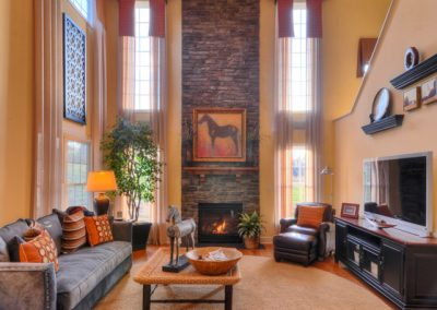 two story room with stone fireplace and ceiling beams
