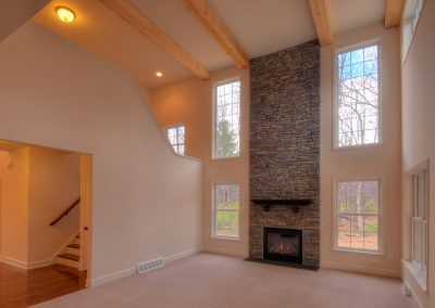 two story family room with ceiling beams and stone fireplace