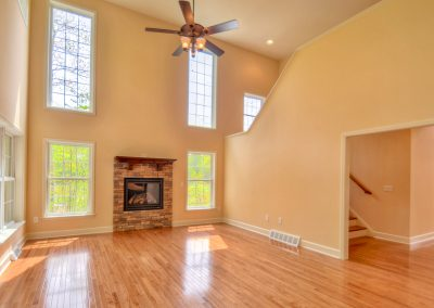 two story family room with short stone fireplace