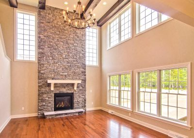 two story stone fireplace and chandelier