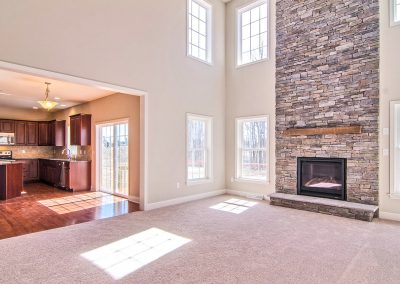 two story room with stone fireplace