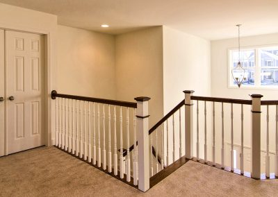 upper landing with wooden railings overlooking foyer