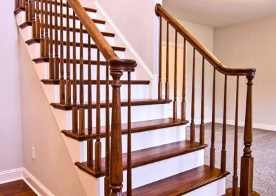 wooden staircase with rounded first step