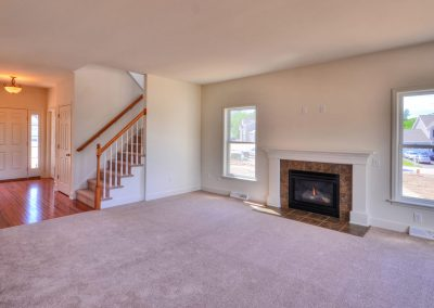 the family room with fireplace in the edison single family home