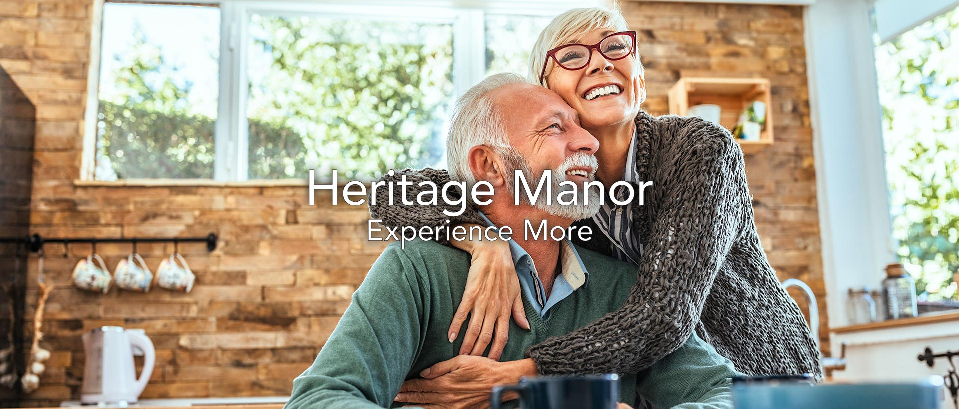 older couple smiling in their kitchen and enjoying life at heritage manor